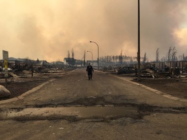 "In this image released by the Alberta RCMP on May 5, 2016, a police officer walks on a road past burned down houses in Fort McMurray, Alberta. Canada prepared to airlift to safety up to 25,000 people who were forced from their homes by raging forest fires in Alberta's oil sands region, and now risk getting trapped north of Fort McMurray. / AFP PHOTO / Alberta RCMP / RCMP / RESTRICTED TO EDITORIAL USE - MANDATORY CREDIT ""AFP PHOTO / ALBERTA RCMP/ HO"" - NO MARKETING NO ADVERTISING CAMPAIGNS - DISTRIBUTED AS A SERVICE TO CLIENTS"