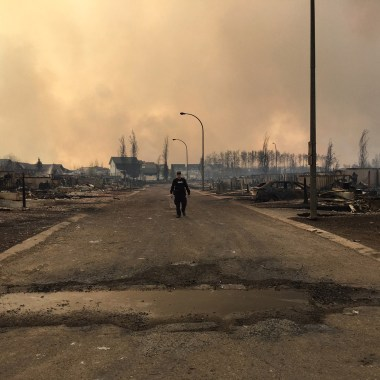 """In this image released by the Alberta RCMP on May 5, 2016, a police officer walks on a road past burned down houses in Fort McMurray, Alberta. Canada prepared to airlift to safety up to 25,000 people who were forced from their homes by raging forest fires in Alberta's oil sands region, and now risk getting trapped north of Fort McMurray. / AFP PHOTO / Alberta RCMP / RCMP / RESTRICTED TO EDITORIAL USE - MANDATORY CREDIT """"AFP PHOTO / ALBERTA RCMP/ HO"""" - NO MARKETING NO ADVERTISING CAMPAIGNS - DISTRIBUTED AS A SERVICE TO CLIENTS"""